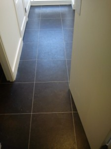 Her we have fully adhered hard vinyl tiles with feature strip to Hallway.