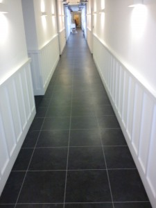 The completed Hallway looks modern and fresh with the black tiles and the grey feature strip to finish.